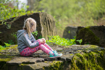 Dziewczynka na kamieniu w lesie