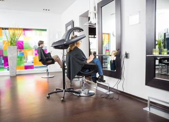 Customers Undergoing Hair Treatment In Salon