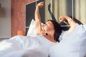 young woman waking up stretching in bed at home