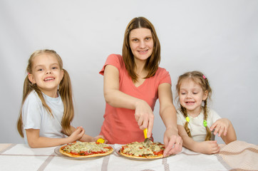 Mother and two little daughters happy sitting at a table with two pizzas