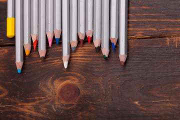 colored pencils laid out on the old brown boards. The workplace of the artist