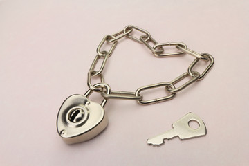 Heart shaped padlock and chain with key on a pink paper background