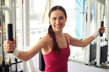 Smiling girl is working out on butterfly machine in gym near win