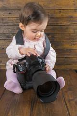 Bebé fotógrafo con una cámara réflex profesional ajustando parámetros para hacer una fotografía