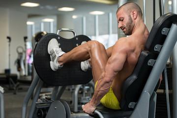 Bodybuilder Doing Leg Press Exercises On Machine