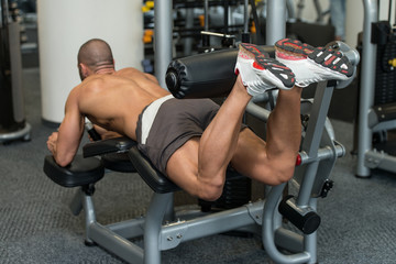 Bodybuilder Doing Lying Leg Curls Exercises On Machine