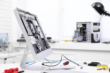 Disassembled computer monitor on table in service center