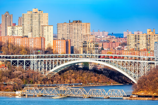 Henry Hudson Bridge spans Spuyten Duyvel Creek, in New York City. Harlem apartment buildings shine under the late afternoon light.