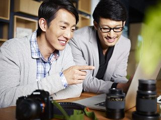 two asian photographers designers working in studio