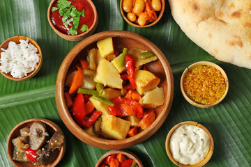 Stewed vegetables with spices and flat bread on banana leaf background