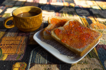 Bread with strawberry jam and coffee on the white plate in morni