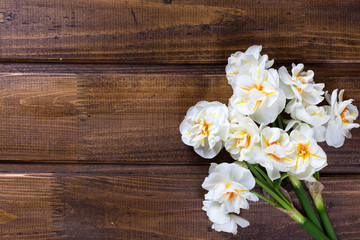 White  daffodils flowers  on brown painted wooden planks.