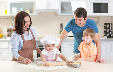 Young parents watching their son to roll out a dough, close up
