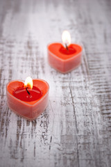 Red burning heart shaped candles on rustic white wooden table.