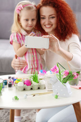 Mother and daughter making selfie while decorating Easter eggs, indoors