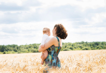 Beautiful woman playing with her infant baby in a meadow of whea