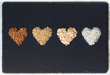 Buckwheat, brown rice, oatmeal and milk rice in a shapes of hearts