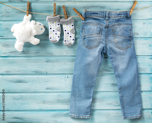 8595b5a3d Baby boy jeans, socks and white toy bear on a clothesline