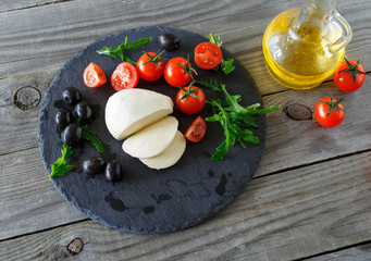 mozzarella cheese with cherry tomatoes, arugula and black olives
