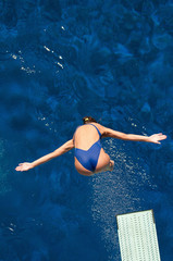 Wall Mural - Diving from springboard, female diver in the air.