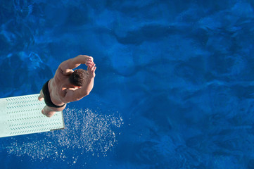 Wall Mural - Springboard diving. Male diver bouncing on the springboard before the jump