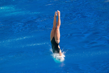 Breaking the surface. Female diving champion entering the water with minimum splash