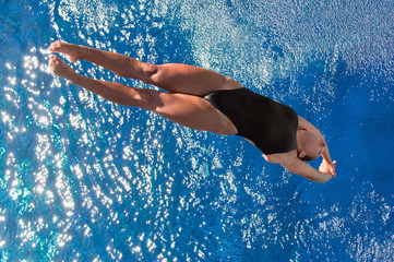Wall Mural - Diving woman. Attractive girl diving into the pool. Shot from above