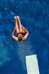 Wall Mural - Springboard diving. Female diving champion dives from springboard, doing back flip. Shot from above