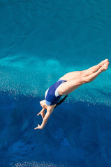 Wall Mural - Female diving. Lady diver in the air above the swimming pool