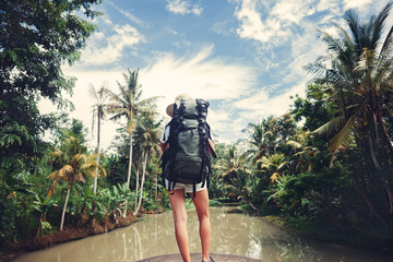Woman with backpack standing near big tropical river and looking far away