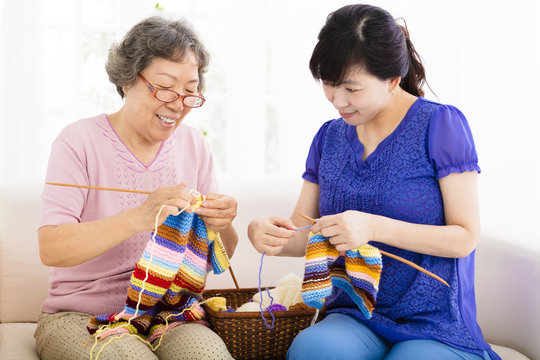 happy Senior mother and  daughter  learning knitting