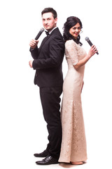 The Showman and showwoman. Young elegant man  and woman holding microphone against white background. Showman concept.
