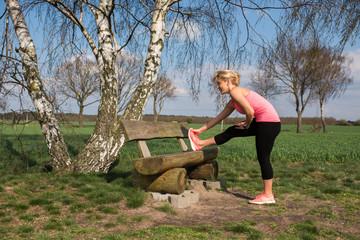 Joggerin macht Dehnübungen an einer Bank auf einer Wiese im Frühling