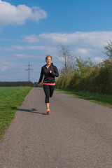 Joggerin läuft auf asphaltiertem Weg im Frühling