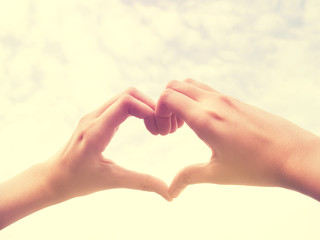 Vintage style  photo of healthy female hands in  form of heart shape.