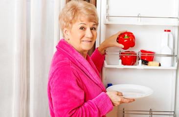 Senior woman taking a red paprika from fridge