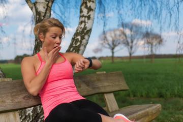 Joggerin schaut erschrocken auf ihren Fitness Tracker
