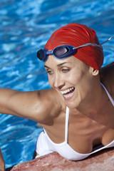 portrait de belle femme souriant dans l'eau au bord d'une piscine