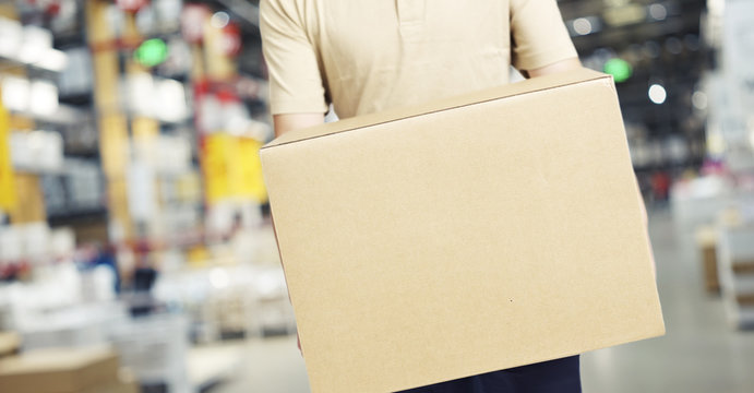 male warehouse worker carrying a carton box