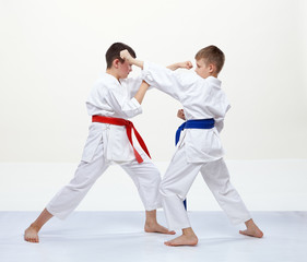 On a white background athletes train blocks and kicks of karate