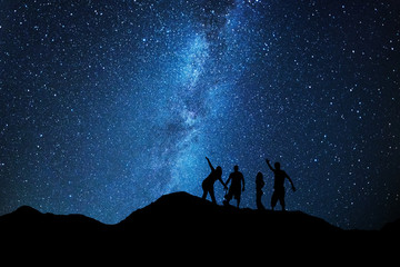 Peoples admiring the milky way in a night full of stars