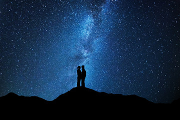 Couple of lovers kissing under the milky way
