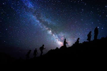 Group of mountaineers who climb the mountain top under the milky way