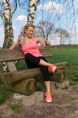 Joggerin auf einer Holzbank hält eine Wasserflasche und schaut auf den Fitness Tracker