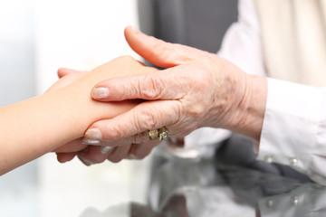 Pomocna dłoń. Dłoń starszej kobiety przytula dłoń dziecka