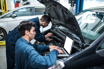 Mechanics examining car engine using laptop