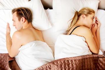 Young offended couple lying back to back in bed