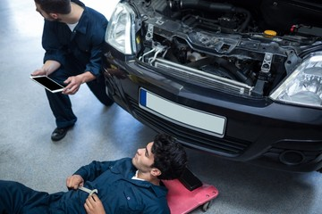Mechanics repairing car