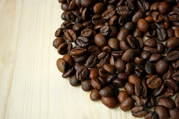 Coffee beans on wooden surface.