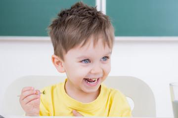 lachender kleiner junge beim malen mit dem pinsel